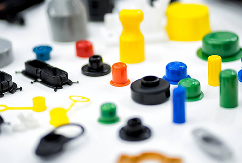 Yellow, black, green and blue precision plastic parts made by Drimo Plastics