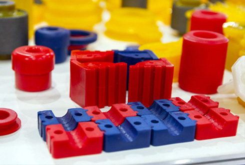 Red, blue and yellow precision plastic parts made by Drimo Plastics